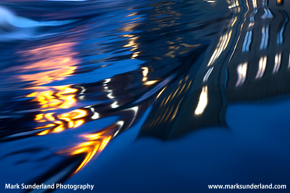 Abstract Reflection of New Mill and Lights in the River Aire Saltaire West Yorkshire England